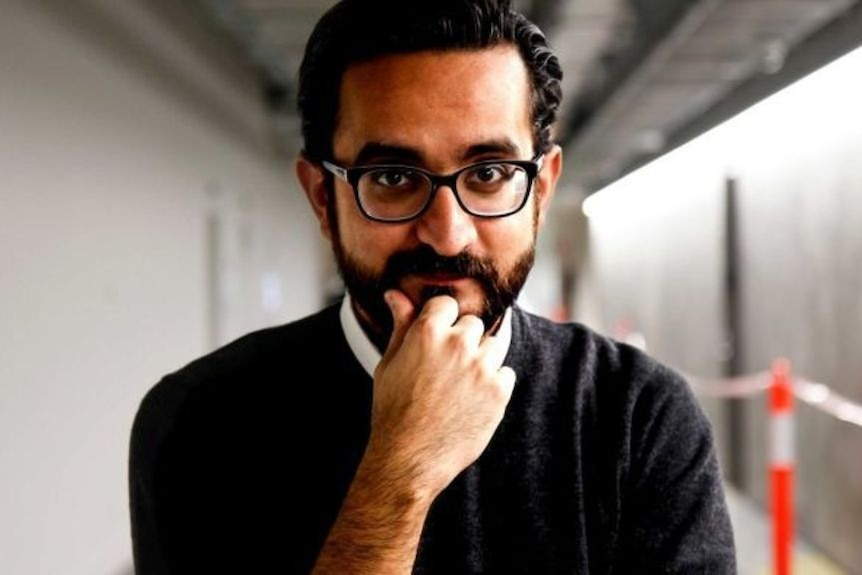 A man wearing glasses look straight ahead with his hand on his chin.