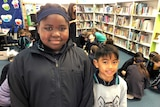 Students Sohaiba Mustafa and Christian Buelva standing in the school library with other students and books in the background.