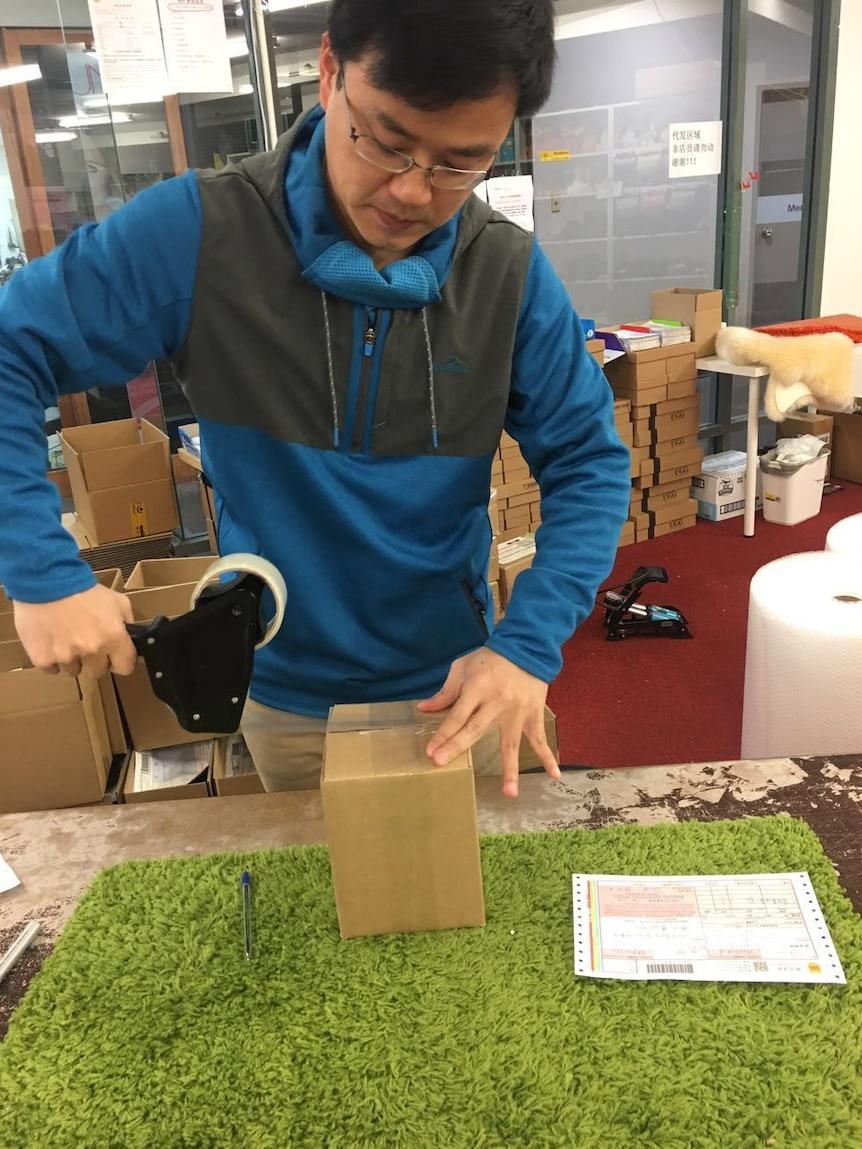 Ming Ouyang packs an order for a customer.