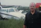 Mike Willesee stands in the rain in front of a crashed plane. People hold umbrellas in the background