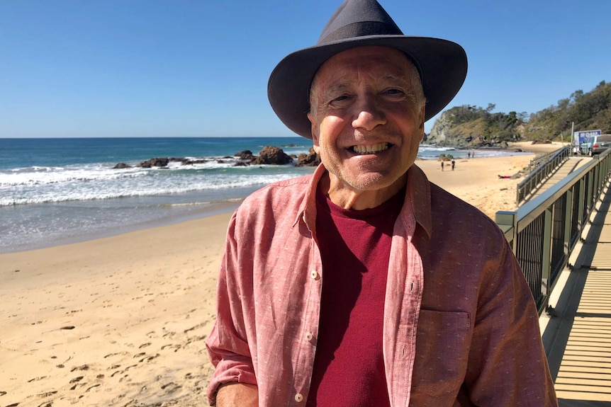 An older man wearing a pink shirt and hat stands smiling next to a beach with the ocean in the background.