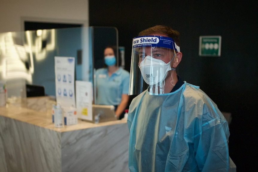 A man wearing full PPE and a woman in the background behind a screen.