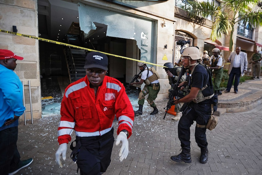 Security forces surround a hallway behind a shattered door in which an unexploded grenade lies.