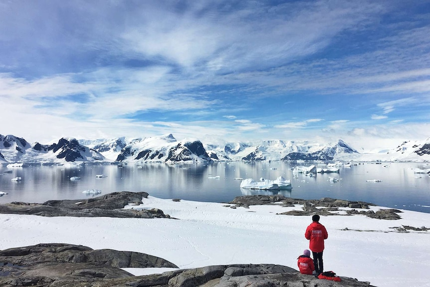 Two people sit on the ice in Antarctica