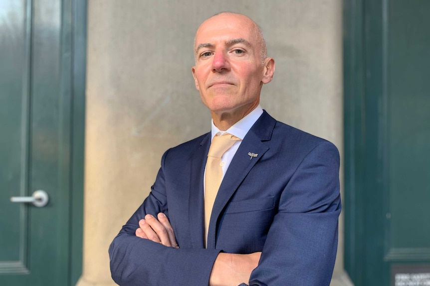 Silvio Del Vecchio stands with his arms folded wearing a blue suit and pale yellow tie