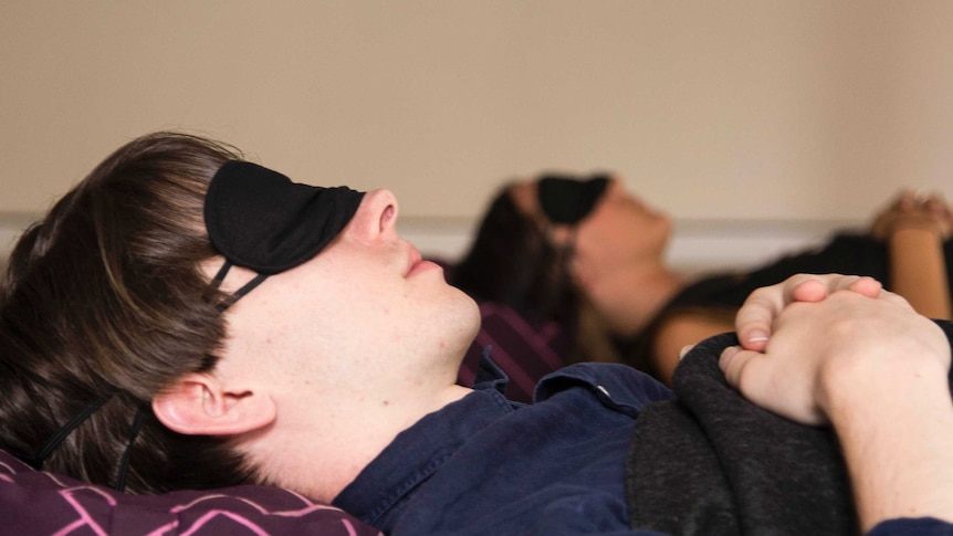 A man and a woman sleep in a guided nap class, Sydney, 2017