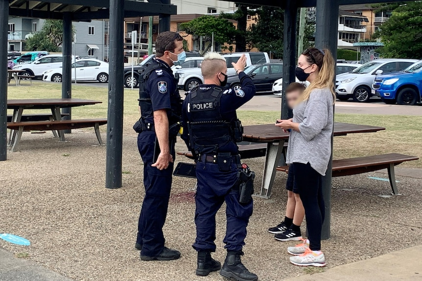 A pair of Queensland police speak to a woman in a park.