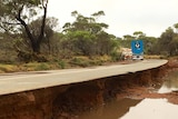 A long stretch of road that has been heavily damaged by flood water.
