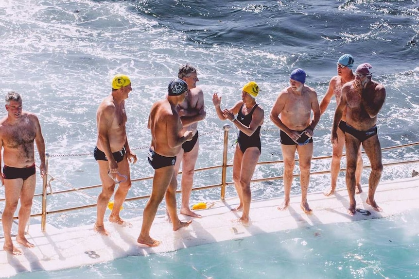 Swimmers of mixed ages stand at the edge of an ocean pool, about to race.