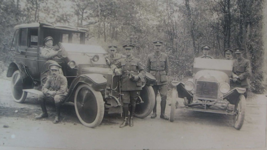 A black and white photo of eight men in Red Cross uniforms, standing around two cars during World War One.