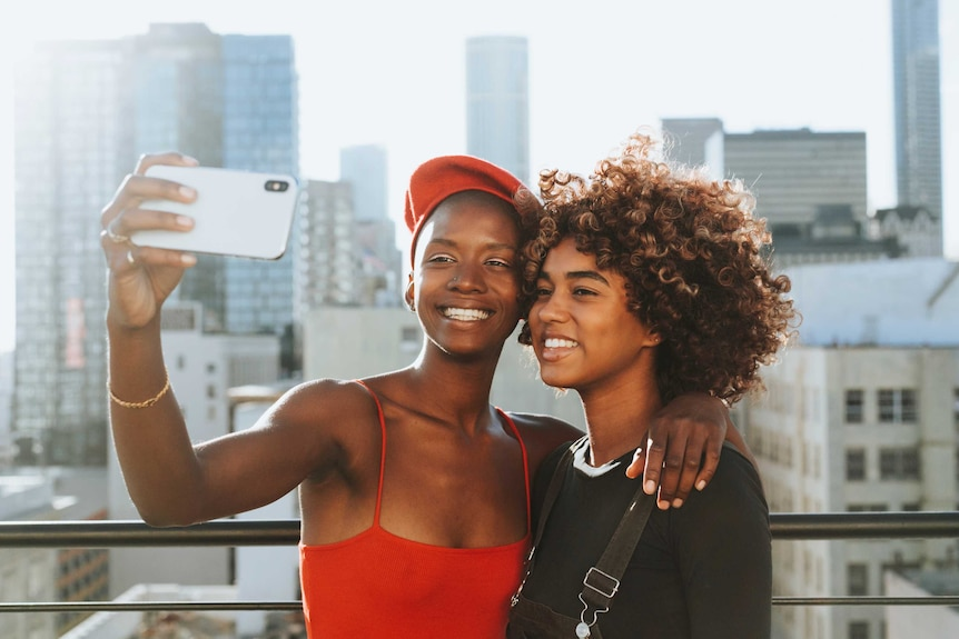 Two teenagers smile and take a selfie