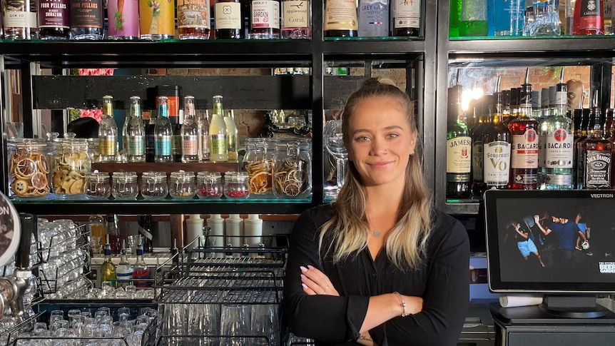 A woman with her arms folded standing behind a bar.