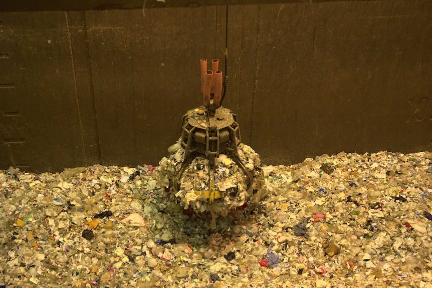 A crane collects a large amount of rubbish from a pile