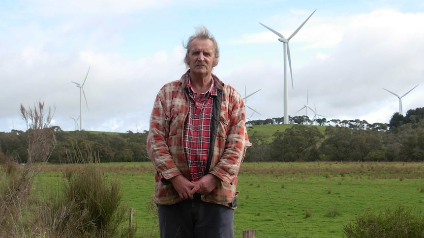 Man stands on his property with wind turbines in the background