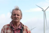 A man stands on his property with wind turbines in the background.
