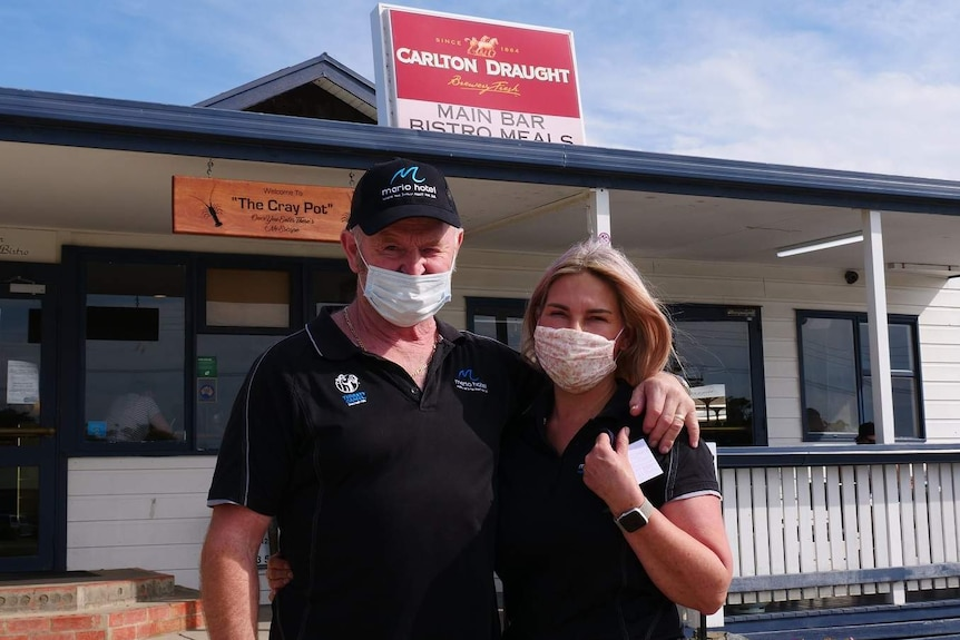 A man and a woman, both wearing masks, stand outside a pub.