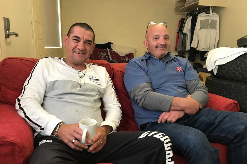 Two men sit on a couch in a shared house
