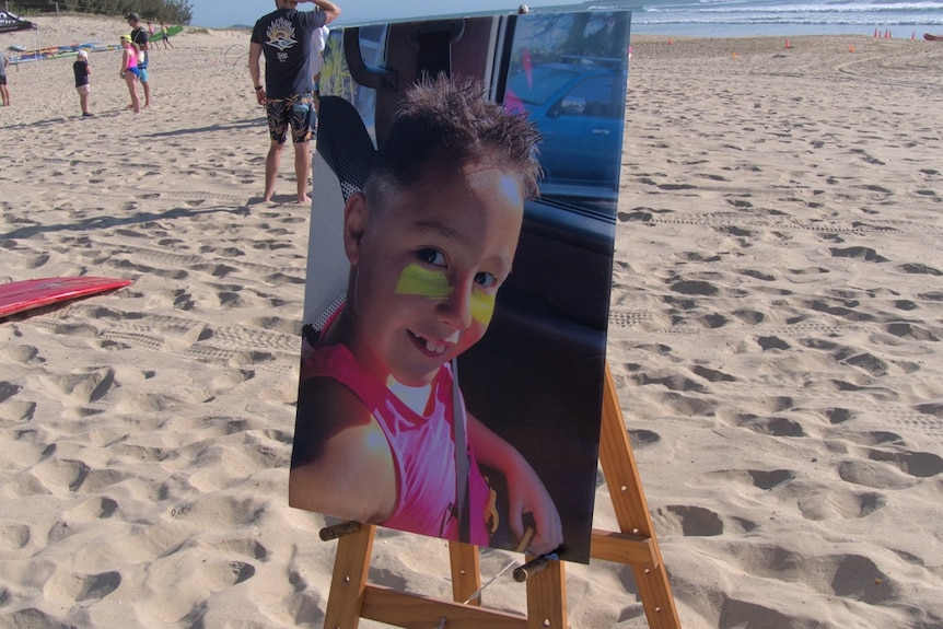 A large photo of a boy in a fluoro nippers vest mounted on an easel on a beach.