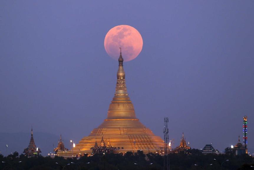 Themoonrises behind the Uppatasanti Pagoda seen from Naypyitaw, Myanmar.