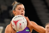 A Queensland Firebirds Super Netball player looks to pass the ball against the Giants.
