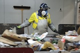 A man wearing a cap, mask and goggles stands at a conveyor belt sifting rubbish.
