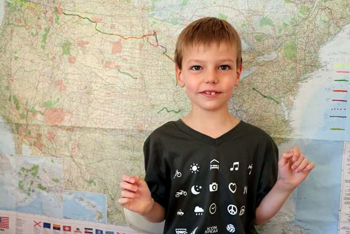 A child in front of a map of the United States of America.