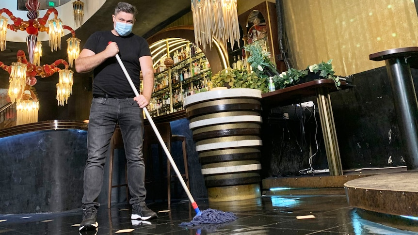 Geoff Slater, owner of Laruche nightclub, wearing a mask while cleaning the floor