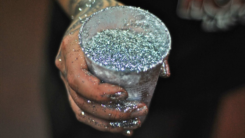 A woman holds a cup full of silver glitter.