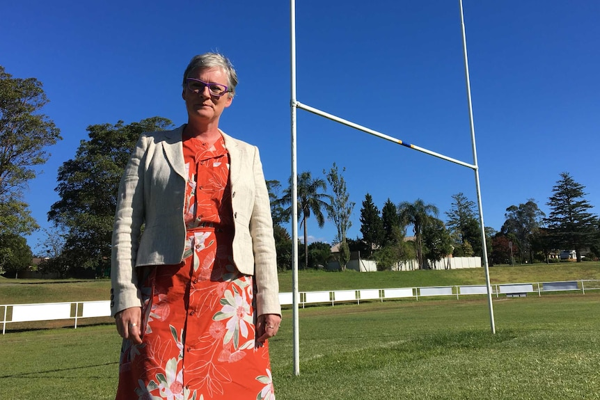 .A woman stands on a sporting field in front of the football goal and stands.