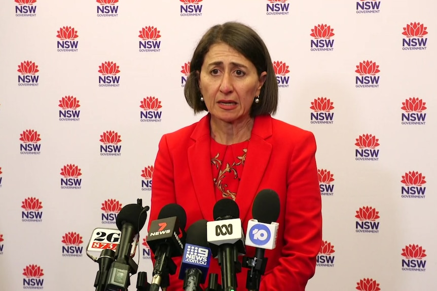 NSW Premier Gladys Berejiklian stands at a lectern with microphones pointed at her.