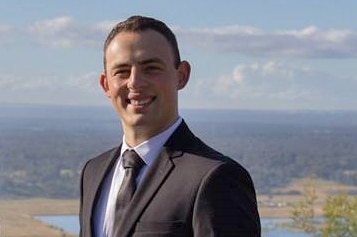 A man in a suit poses in front of a scenic view