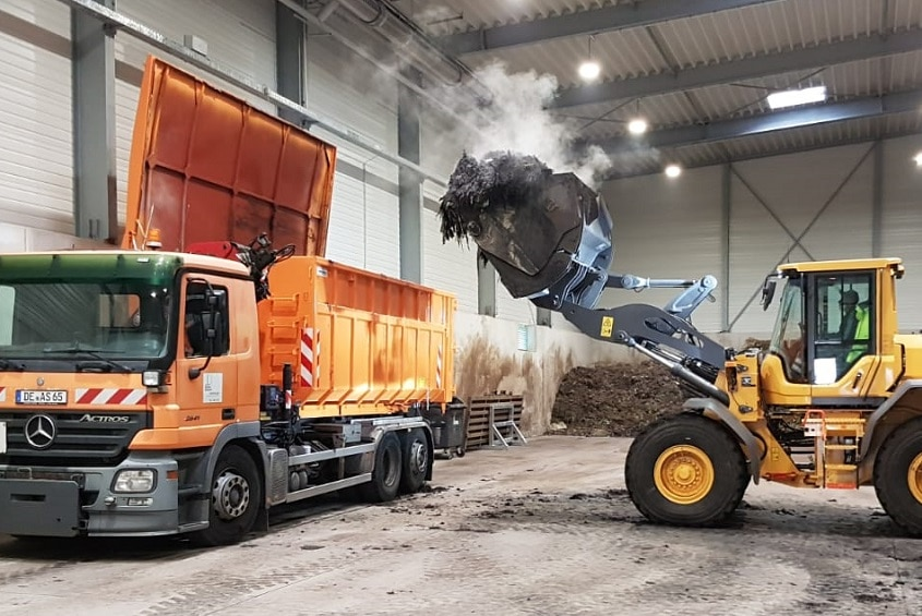 A tractor loads rich compost into a waiting truck from a pile stored in a big warehouse
