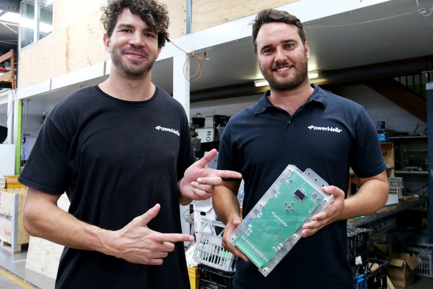 Two men hold up a power bank.