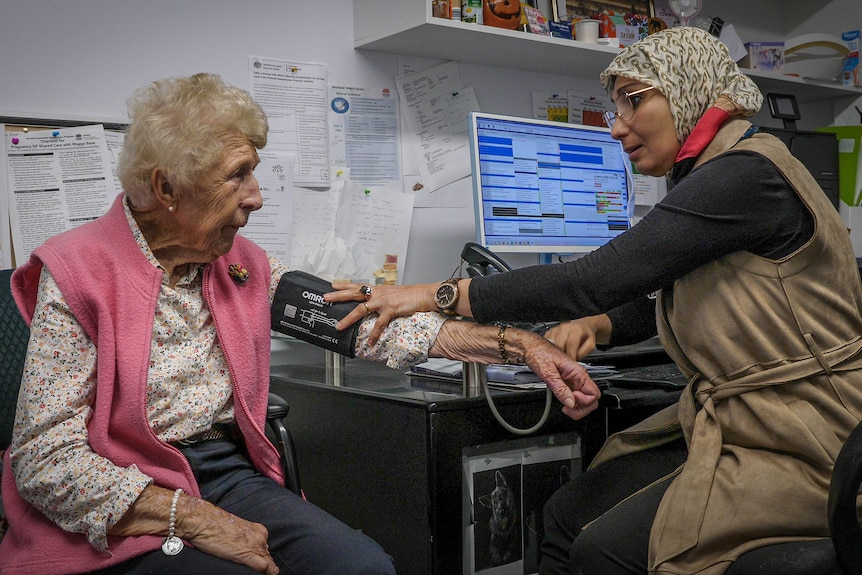 A woman wearing a patterned hijab take the blood pressure of an elderly woman wearing a pink vest.