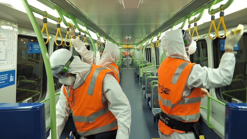 People in orange high-vis vests and PPE equipment sanitise a train carriage.