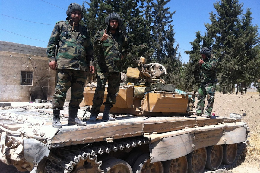 Syrian soldiers stand on a tank near Damascus