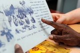 A hand pointing at a page in a book