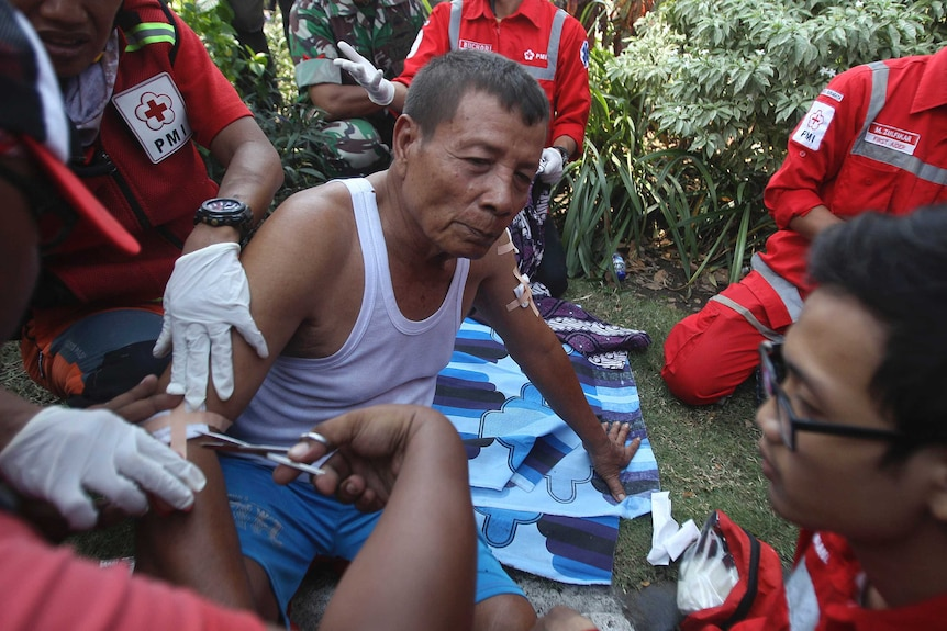 A man in a singlet and shorts is treated for a wound on his arm by three people in medic uniforms