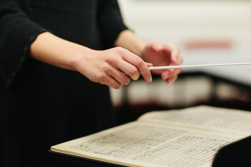 Close up of Nicky Gluch's hand conducting, hovered over a music sheet.