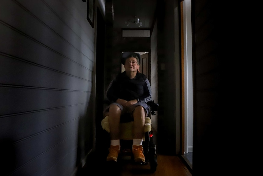 Man sits in dark hallway in wheelchair, with hands folded on lap, wearing orange shoes