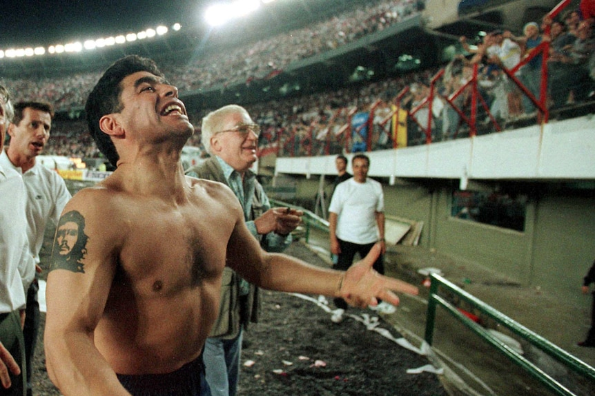 Shirtless Diego Maradona celebrates in front of the stands.