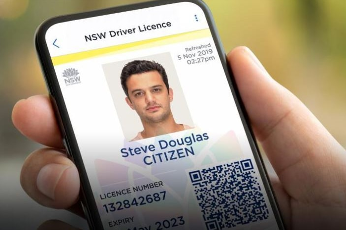 A person holds a mobile phone in their hand with the screen open to a digital licence with driver's photograph.