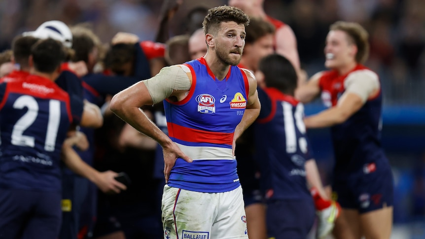 A dejected AFL star stands with hands on hips as opposition players celebrate a grand final win in the background.