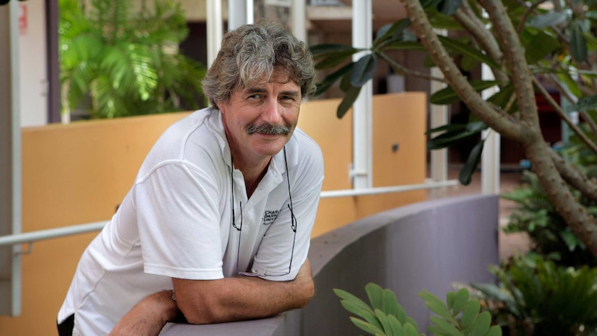 A man with a moustache and a white polo shirt leans on a ramp at Charles Darwin University.