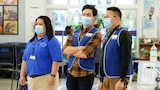 Three store employees in blue uniforms wear masks while at work.