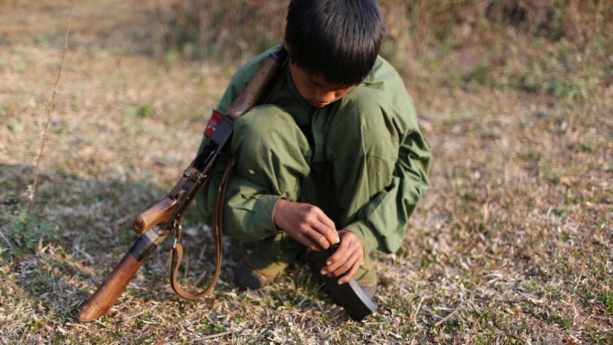A 15-year-old child soldier in Myanmar loads a gun