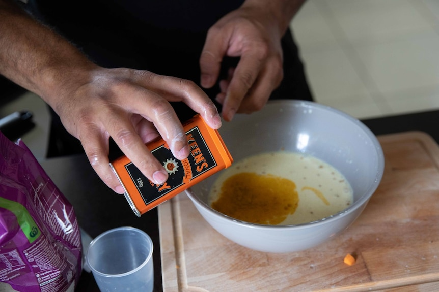 A pair of hands pours curry powder into a bowl of cream liquid