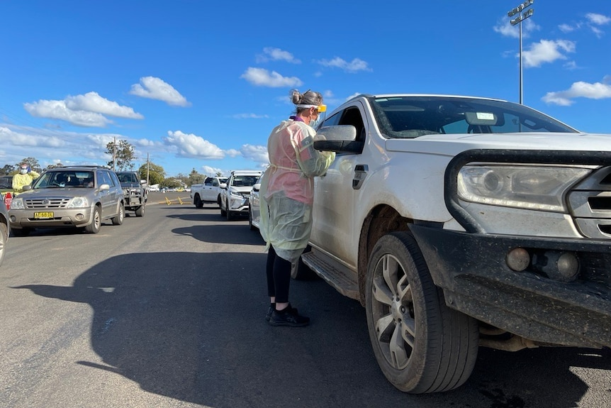 A woman in protective clothing speaks to a passenger of a four wheel drive vehicle
