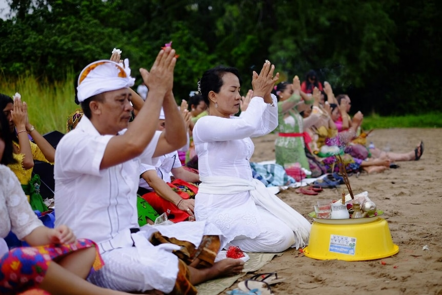 A line of Balinese people sitting in the sand dressed in traditional costumes as they pray.