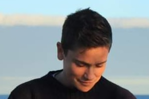 Close up shot of Kaya Wilson, with short dark hair and in black jumper, looking down and smiling slightly. The ocean is behind.